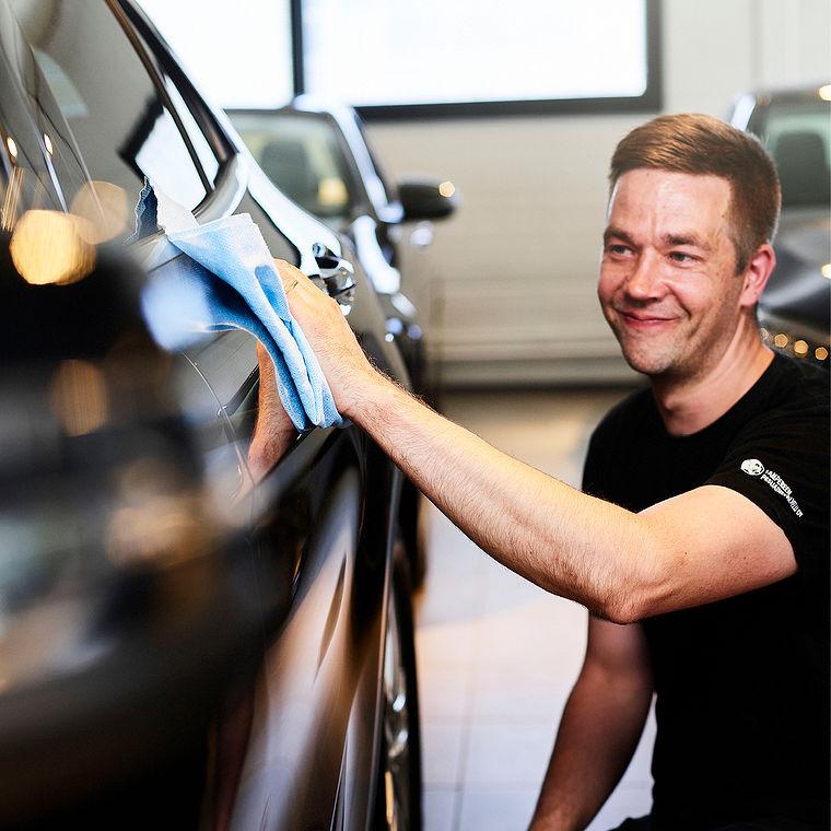 Kuvitusvalokuva nettisivustolle autoa myyntiin viimeistelevästä työntekijästä